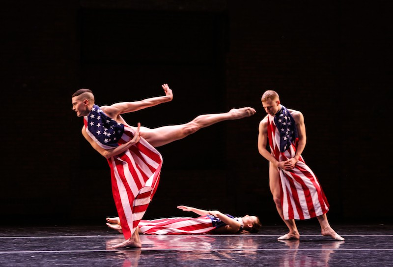Three dancers where American Flags tied around their necks. One dancer executes a high arabesque. Another lies prone on the floor while the third leans on his right side.