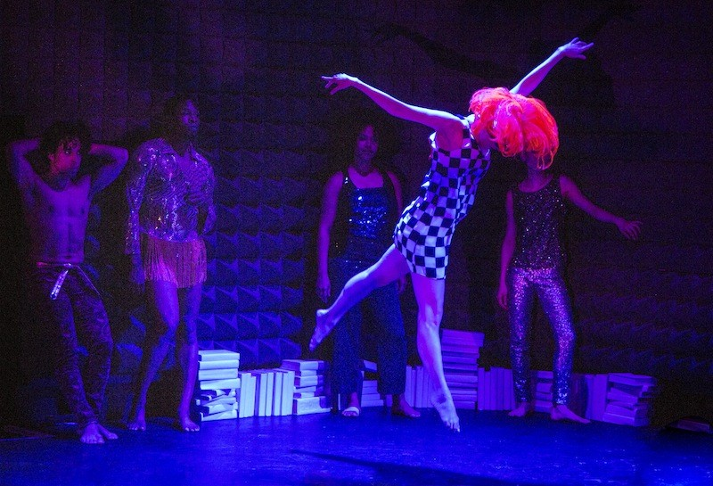 A woman in a bright orange bobbed wig jumps in the air while other performers in sequins lean against a wall. Books litter the stage floor