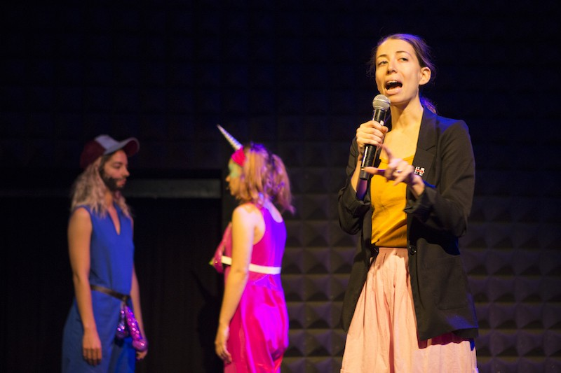 A woman in a black blazer talks to the audience while two women in brightly colored costumes are in the background. One has a drawn on brown beard.