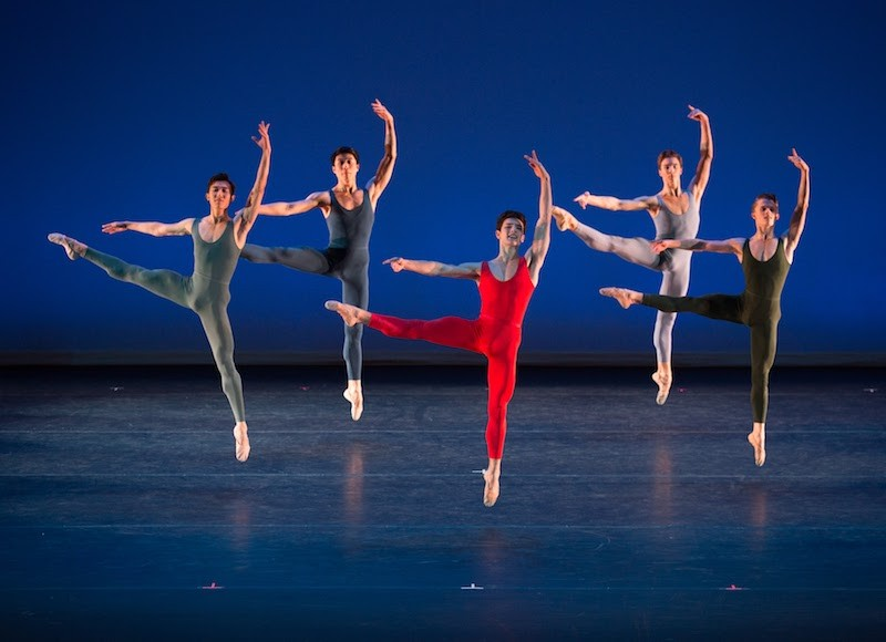 A male quintet, each in a primary color unitard jump off one leg. The other is pointed out the side. Their left arm is above their head.