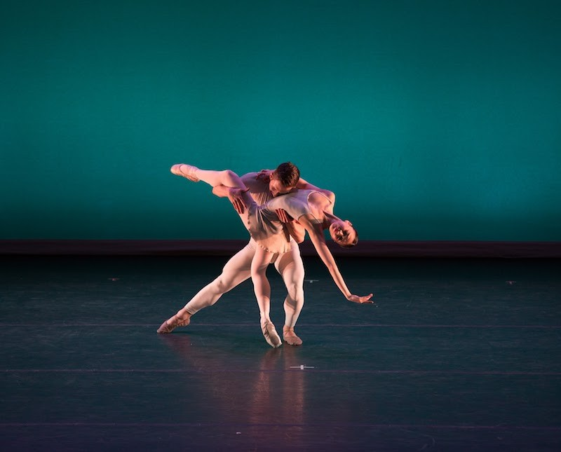 A woman executes a dramatic back bend on demi pointe while her partner lays his head on her chest