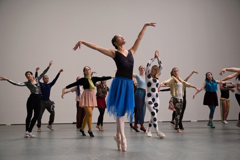 A woman in a blue skirt, black leotard and pointe shoes leads a group of MoMA employees in a dance