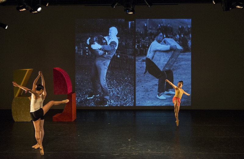 Three women dance on pointe as a black and white film projects behind them and two brightly colored larger-than-life shapes sit upstage