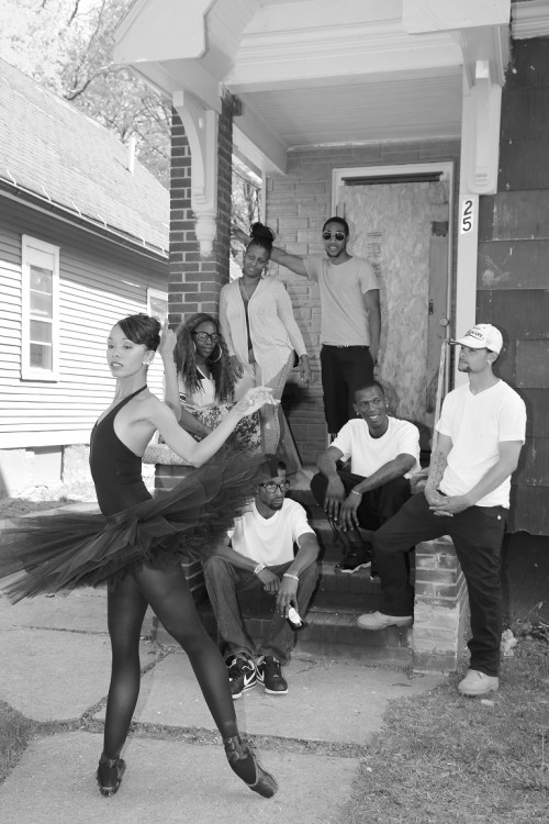 Ash in a black tutu, tights and point shoes. A group of community members of different ages observe her on a porch.