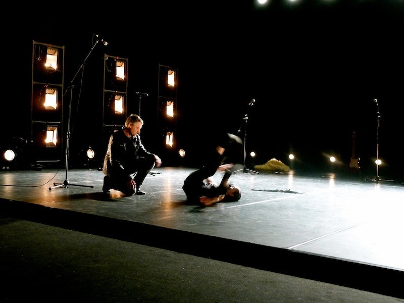 Damiano Fao crouches as he watches his collaborator Laura Simi perform a dance move on her back with her legs in the air