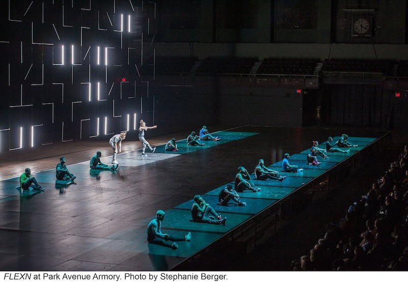 Two lines of seated FLEXN dancers, each in their own pool of light which denotes a prison scene
