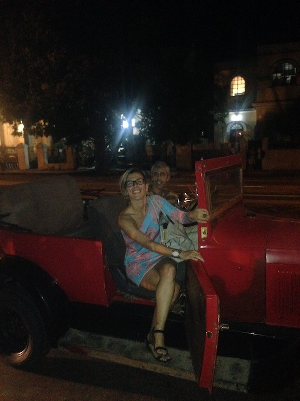 People in a red vintage convertible at night in Havana