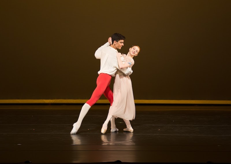 Two Dancers hold one another as if they are going to engage in a waltz. His foot points behind him while her foot points to the front.