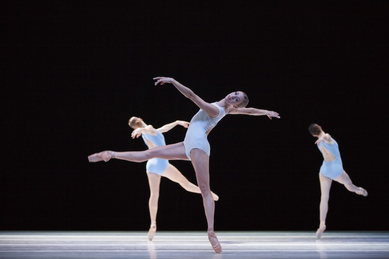 three dancers in white leotards balance on pointe. The woman in front looks out to the audience as she extends her back behind her