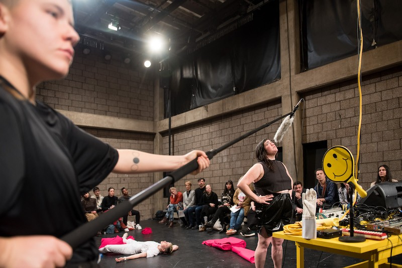 Jen Rosenblit speaks into a boom mic which is held over her head by a performer who wears a black t-shirt. Other performers are in the background laying down with the fuchsia fabric