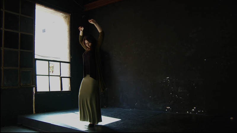 A young women in a dim studio practices flamenco in a long taupe skirt and dark sweater
