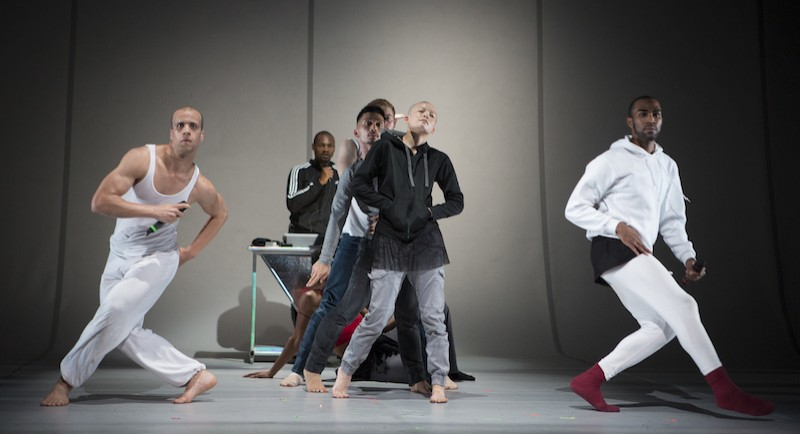 Two dancers in white with microphones. Another in a hoodie posturing in the background.