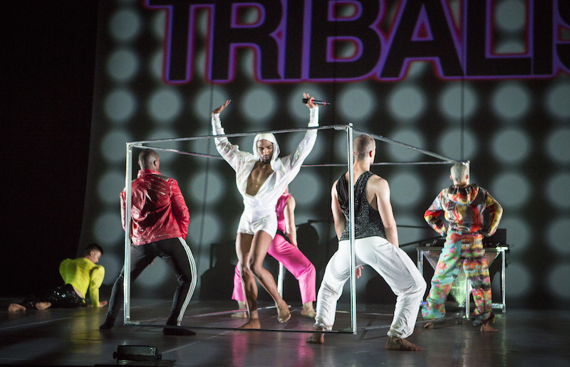 Dancers surrounding a pole structure resembling a boxing ring. They wear colorful  in neon costumes