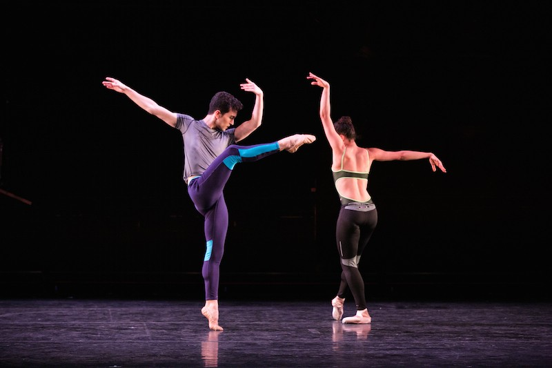 Anthony Huxley balances in an attitude in the front while Rachel Hutsell tendus with her back facing the audience