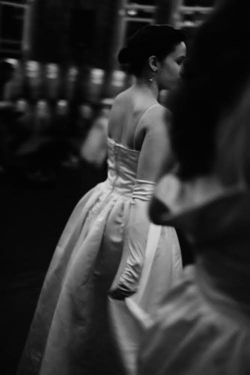 Side profile of dancer in gloves and gown waiting to go on stage