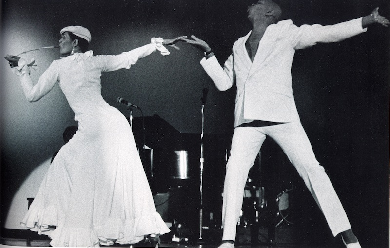 Carmen de Lavallade in a long white dress smokes a long pipe. Her outstretched hand is held by her husband Geoffrey Hold also dressed in white