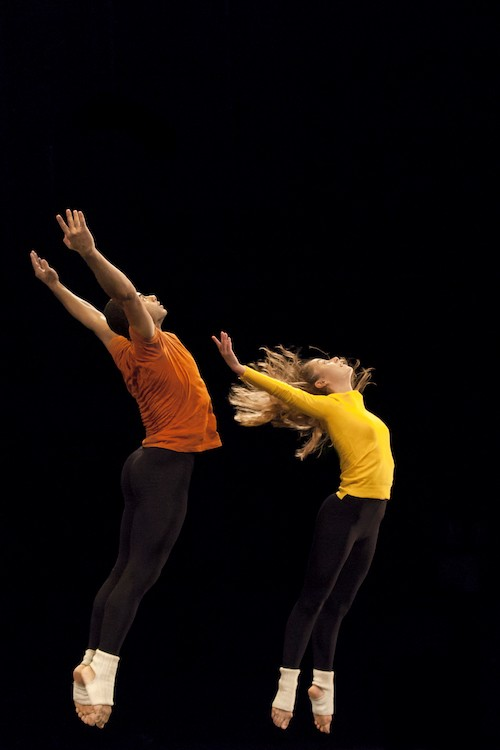 Two dancers in mid air. They arch their upper backs with their hands extending to the ceiling