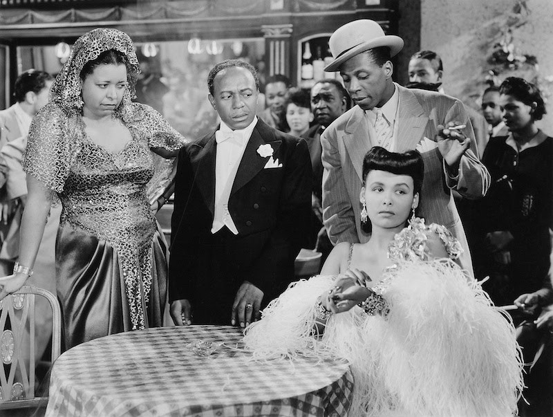 A black and white still from the movie Cabin in the Sky. The stars congreate around a table. A man and woman look incredulously at woman who is seated at the table wearing an evening gown and feather wrap.