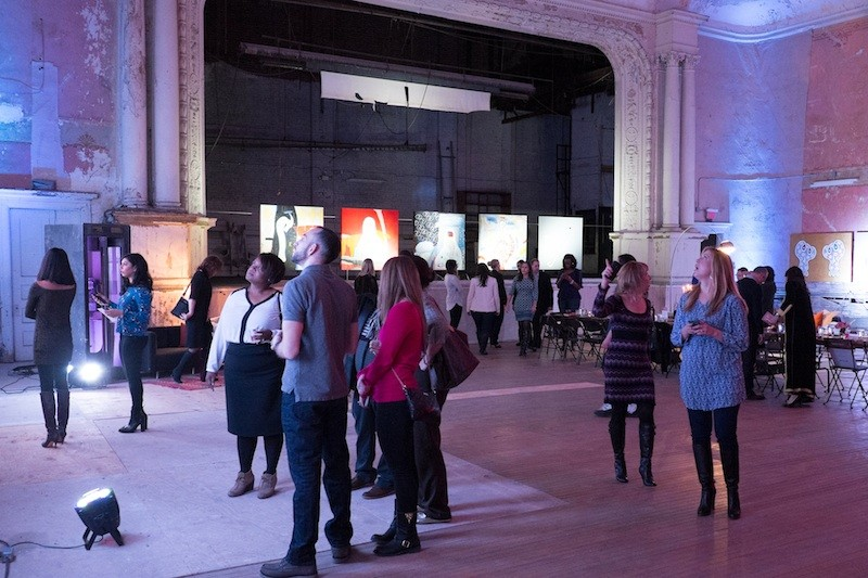 People attend an exhibition in the Carr Center's theater space