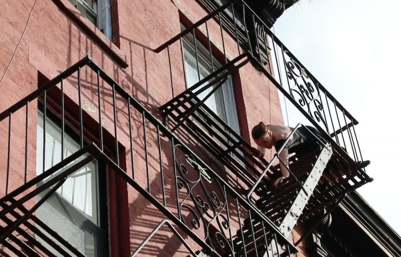 fairskinned woman in a black dress, seated on her black wrought iron fire escape lowering  the upper half of her body on the descending stairs... building is red brick