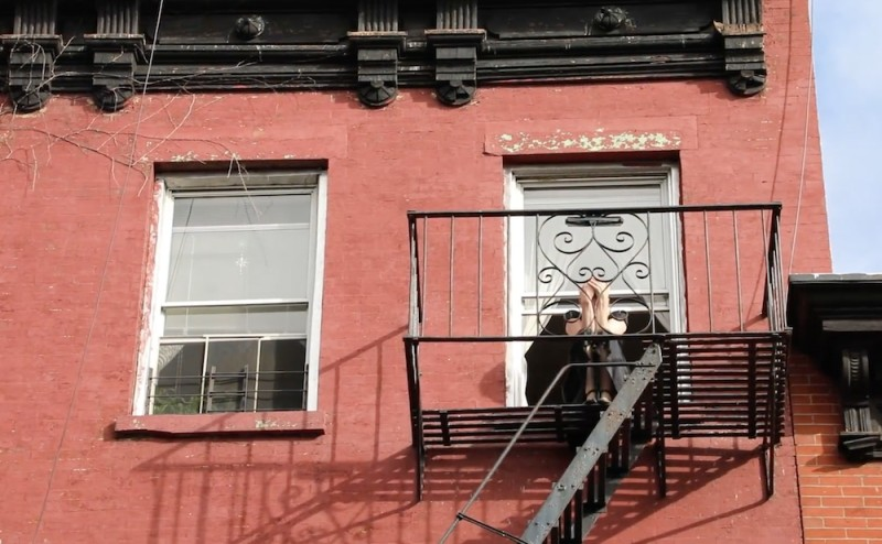 red Brick apartment building, black wrought iron fire escape, fair skinned woman dressed in black clutching her head in both hands as she sits on her window sill