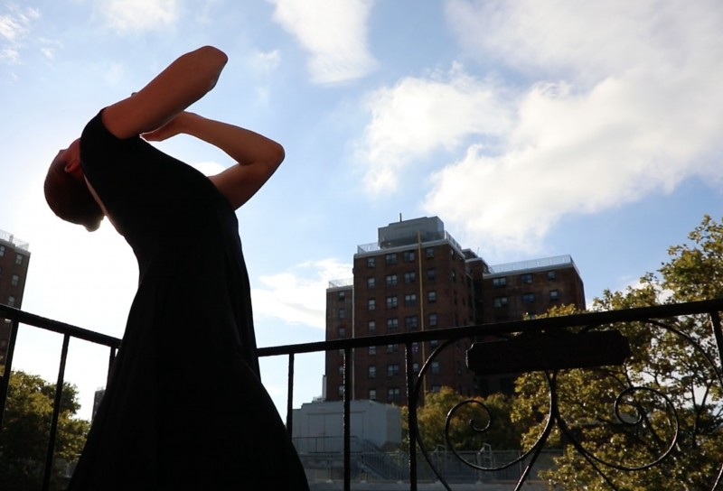 figure in black dress on fireescape reaching out to the blue ski