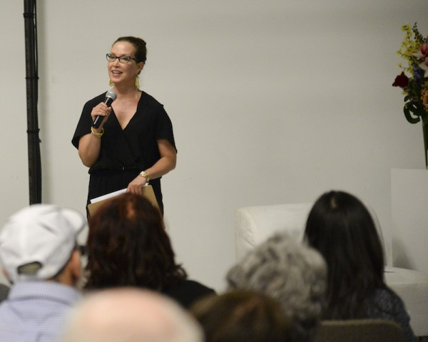 Christine Jowers holds a microphone and talks to an audience during an Enthusiastic Event!