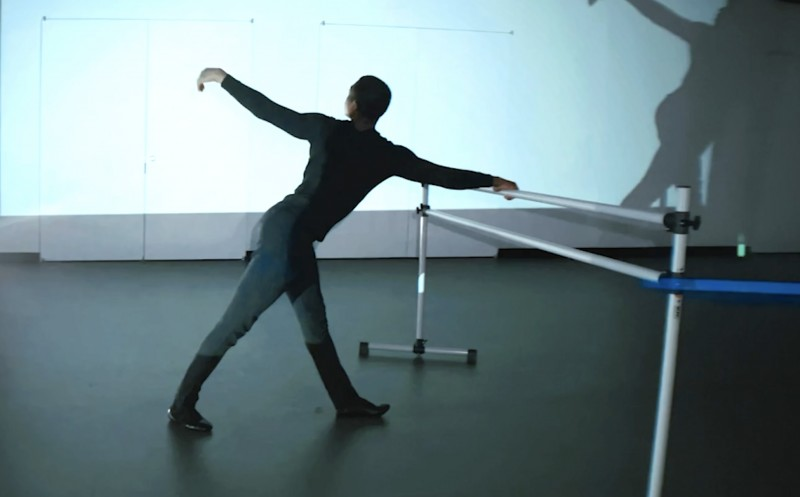 Christopher Grant dances at the barre, his shadow moving with him in the background