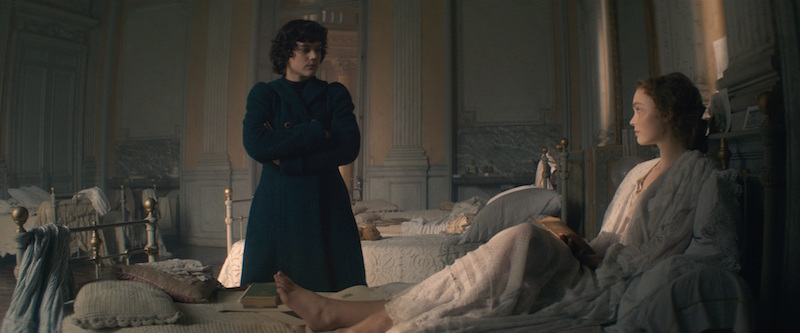 A still of an opulent French bedroom. A person in a dark overcoat looks down at a woman in bed wearing a dressing gown.