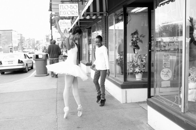 Aesha Ash in a white tutu and pointe shoes on city block. A woman dances next to her high on the tips of her sneakers.
