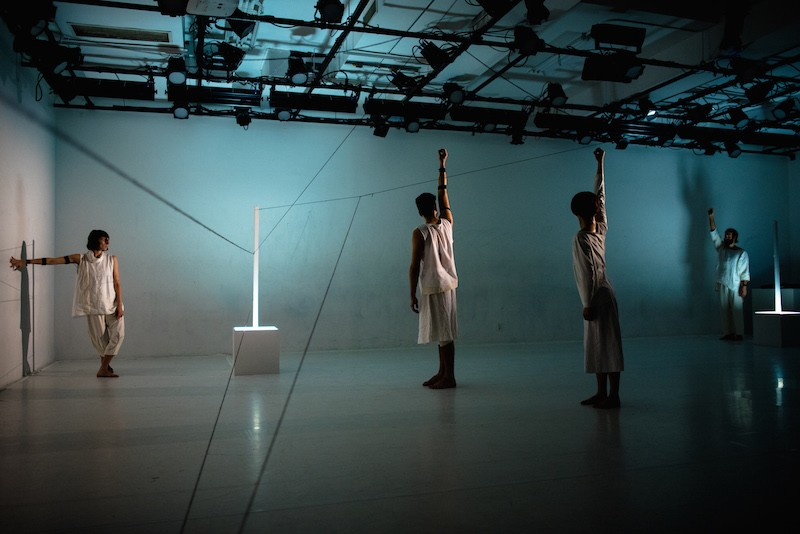 Three dancers stand with the right arms aboce their heads. Light emits from two long sticks that are affixed in cubes. Another dancer traces her hand along the wall.