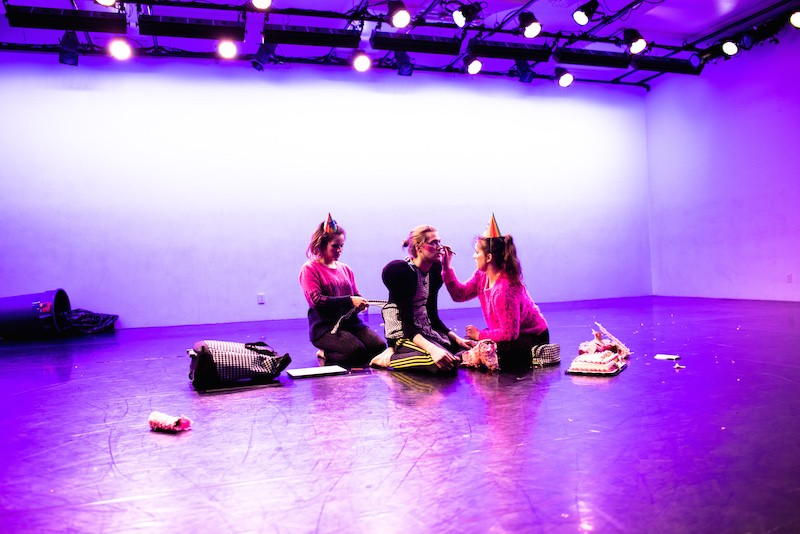 3 dancers sit on the floor wearing party hats. One dancer applies eye makeup to another. A garbage can lays on the ground