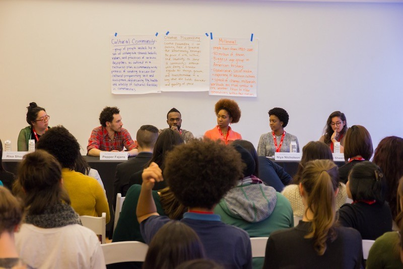 A group of people sit in the audience in front of the Creative Placemaking: The Role of Millennial Artists Panel