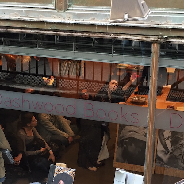 We see Eiko perform in the bookstore through the store's front window. Her hands are raised.