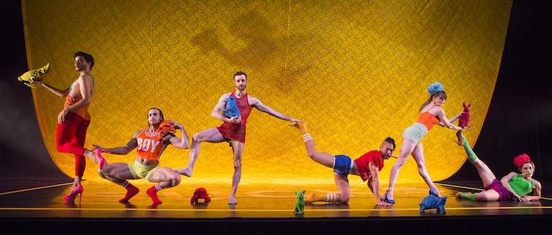 Dancers in colorful athletic wear arrange themselves downstage all connecting to one another in some way. A man wears pink high heals. Another squats turned out will a dancer rests his foot on his thigh.