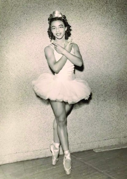 An early image of Delores Brown. She wears a crown in her curly brown hair and dons a white short tutu and pointe shoes. She stand en pointe with her arms crossed over her chest.