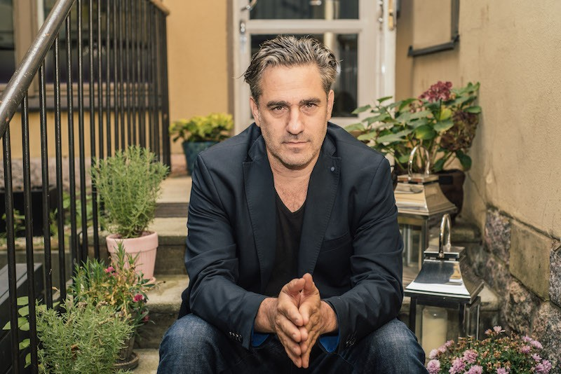 Director Tomer Heymann in a suit jacket and jeans sits on the steps of a porch that is lined with plants. The palm of his hands are pressed together.