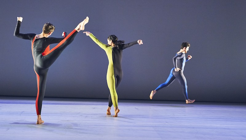 Three dancers in unitards. One lifts her leg to the side and another crosses her legs as her feet are in relve. Both of their backs are to the audience. Another dancer in the background runs to the right.