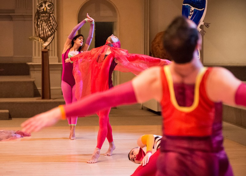 Dancers in purple and red costumes. A dancer in the center wears a gauzy scarf over her head and that drapes over her arms like bird's wings.