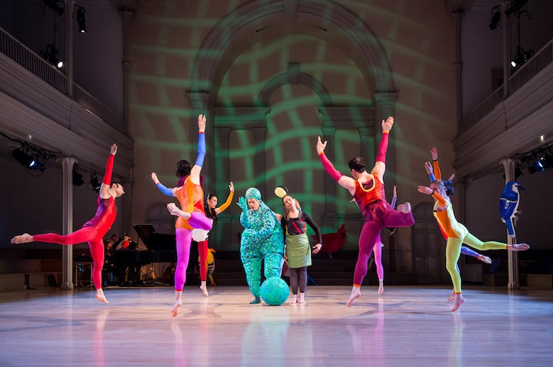 Dancers jump off one leg in a circle. Douglas Dunn in a puffy green costume resembling a monster. A woman in a green skirt and unitard stands next to him.