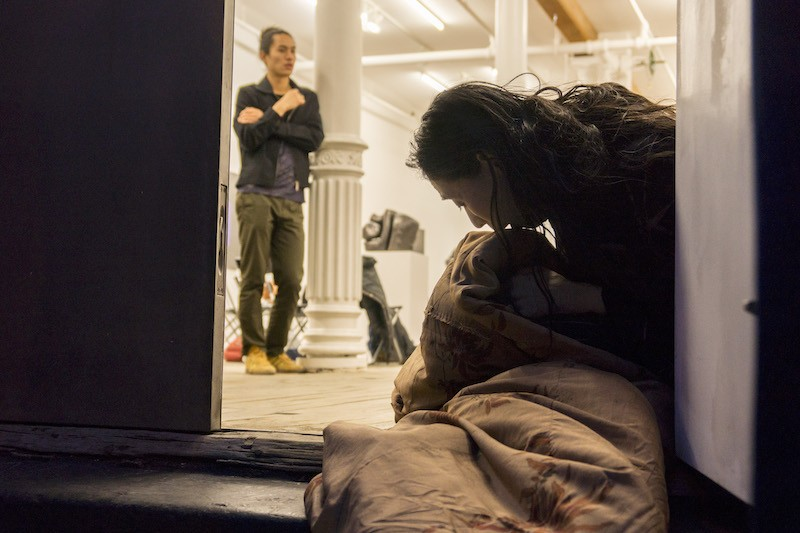 Eiko wrapped up in a blanket while she sits in a doorway
