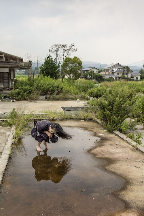Eiko crouches in a puddle on a concrete square in a barren Fukushima