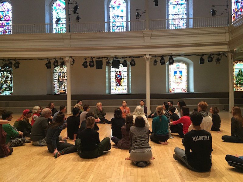 Eiko leads a discussion during her workshop. Participants sit on the floor around her in the space.