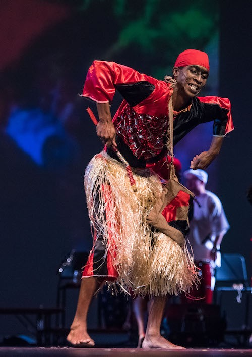 A man in a red and black costume and grass skirt. He hunches his over while his arms are bent the elbows with his hands facing down