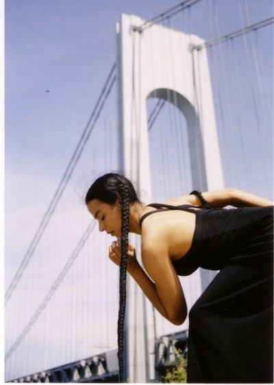 Christa wears a long braid that drapes down to the ground as she assumes a pose. The Brooklyn Bridge is in the background.