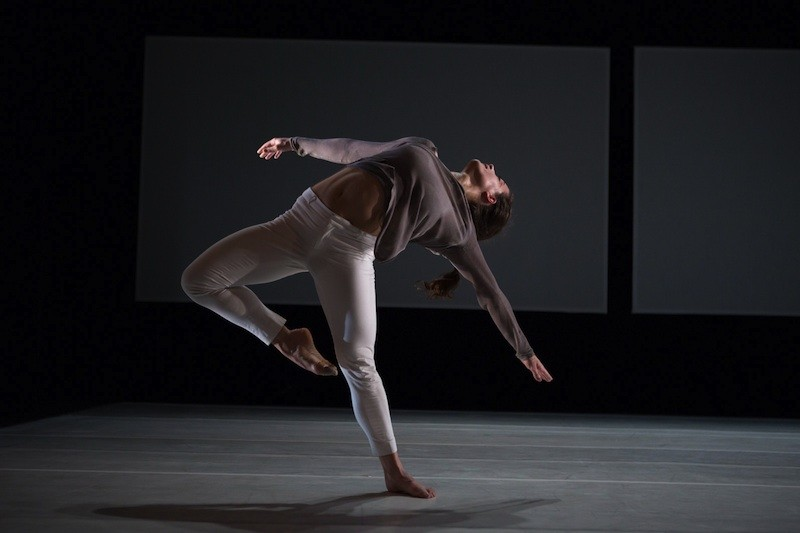 A female dancer suspends backwards on one leg with other leg in passe, her upper body lifts towards the heavens