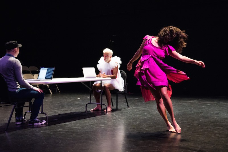Michele Boule, in a fuschia dress, dances in front of two men seated at narrow table with computers in front of them