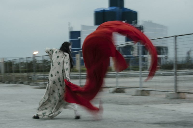Eiko in a kimono with her back towards the camera, her red scarf flaps violently in the wind