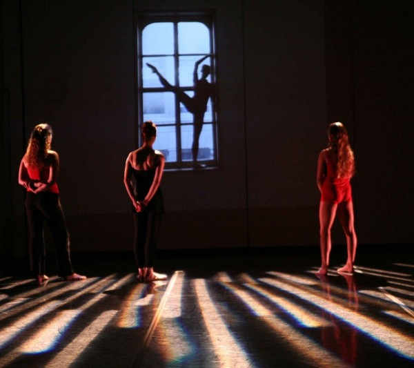 Dancers stand on stage watching a video of a dancer in silhouette extending her leg in front of a window