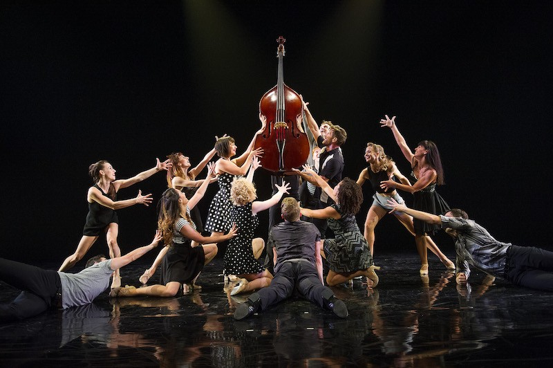 A group of dancers in white and back huddle around a stand up bass. Their arms outstretched around it.